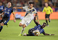 Bacary Sagna #33 of Montreal Impact reaches the ball before Cristian Pavon #10 of the Los Angeles Galaxy