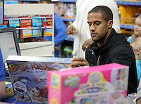 Pictured: Wayne Routledge at the till Wednesday 08 December 2016<br />Re: Swansea City FC players have bought Christmas gifts for 60 children at Smyths toy store in Swansea, south Wales.
