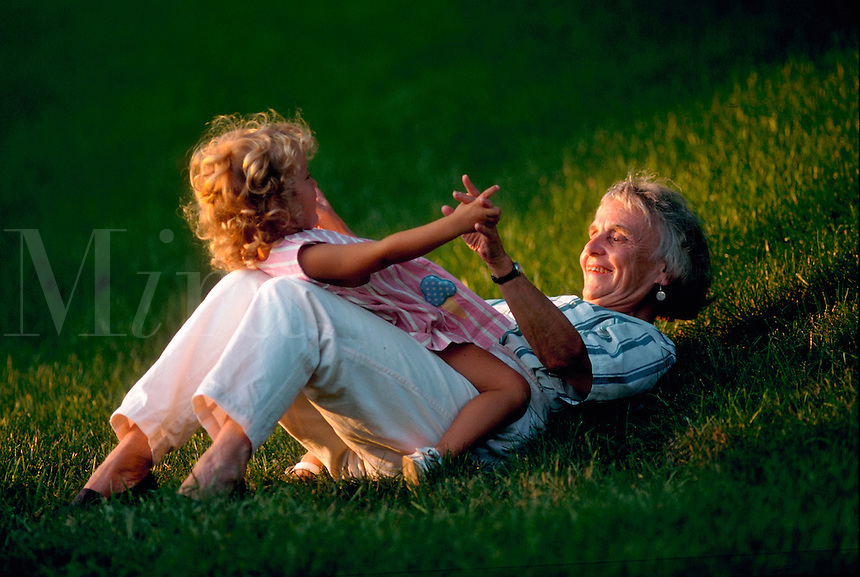 Grandmother plays with young granddaughter outside.