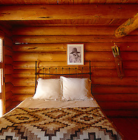 The warm and cosy main bedroom of a traditional log cabin in Colorado