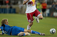 San Jose Earthquakes forward Steven Lenhart (24) slide tackles New York Red Bulls midfielder Mehdi Ballouchy (8). The San Jose Earthquakes tied the New York Red Bulls 2-2 at Stanford Stadium in Stanford, California on July 2nd, 2011.