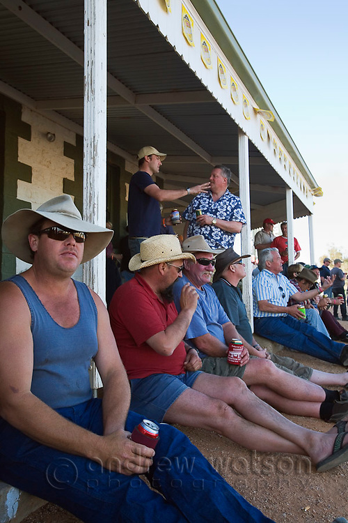 Drinkers sits outside the iconic Birdsville Hotel during the annual Birdsville races.  Every September the small outback town of Birdsville hosts thousands of visitors for the Birdsville Cup, one of the most famous bush carnivals in Australia.  Birdsville, Queensland, AUSTRALIA.