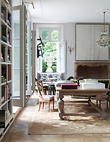 In the family room the atmosphere is light, cool and relaxed achieved by the use of neutral colours and natural materials. Antique pieces mix easily with more modern additions. The built-in floor to ceiling shelving units, set between the French windows, accentuate the ceiling height