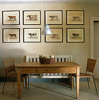 In the kitchen an antique table and contemporary cane chairs are placed beneath a series of prints of cattle