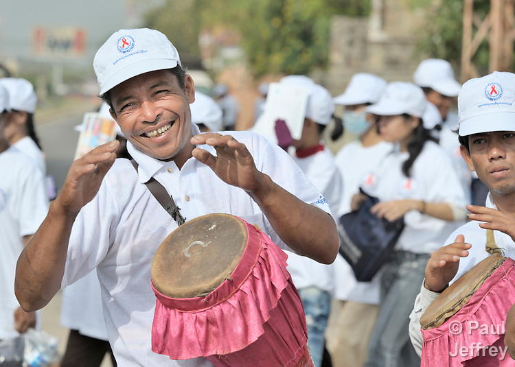 A man plays a drum in a march to commemorate World AIDS Day held in Battambang, Cambodia. Among sponsors of the march was the Salvation Centre Cambodia, an organization that works with Buddhist monks and other activists to foster support for people living with HIV and AIDS as well as public education and advocacy throughout the country.