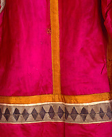 A detail from the back of one of the costumes has a woven geometric band of decoration sewn along the bottom of the vividly coloured garment