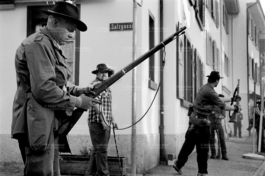 """Switzerland. Canton Basel-Landschaft. Liestal. The celebration of """"Banntag"""" with men shooting their rifles in the air. The """"Banntag"""" is an important day for Liestal municipality and is now a traditional festival in May for the local communities. A 650 years old tradition, where men from the city, some with rifles and others with sticks, walk along Liestal's border to check if the border stones have been moved by the neighbors. Formerly devoted to controlling the location of boundary markers, today it is essentially the occasion for a communal feast.  22.05.2017 © 2017 Didier Ruef"""