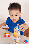 2 year old toddler boyl Asian Chinese American playing with wooden blocks constructing tower vertical