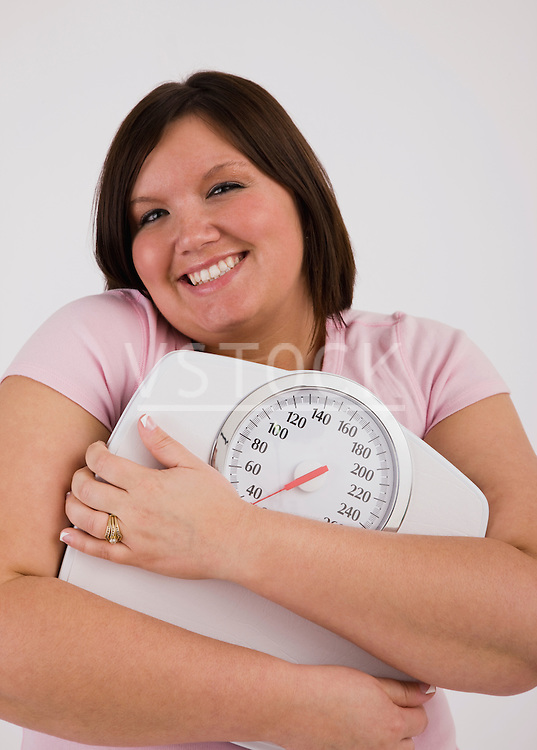 Portrait of young overweight woman hugging scales and smiling