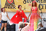 Fashion designer Mariela Caridad (Center) walks with model at the close of the Mariela Color fashion show, during Harlem Week 2017 at 135th Street and St. Nicholas Avenue in New York City on August 19, 2017.