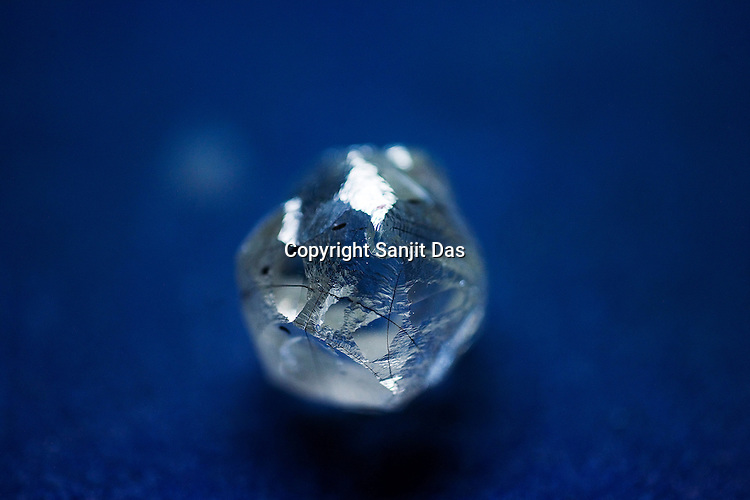 a rough cut diamond is seen in the planning section at the diamond cutting and polishing factory in Surat, Gujarat, Western India.