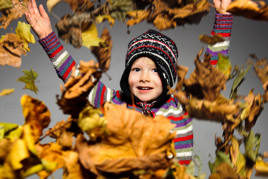 Autumnal (Fall) seasonal image, in the studio, of a boy throwing leaves in the air. Shot with a single Profoto Beauty dish with grid and diffuser using a Batpac battery.