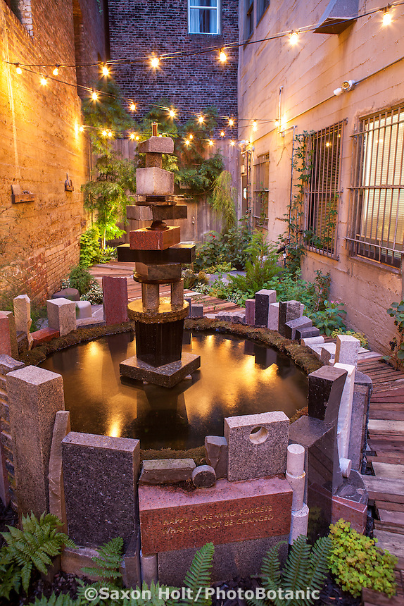 Fountain of recycled granite headstones in evening light in the narrow garden room behind the Mark Twain Hotel; design by Organic Mechanics