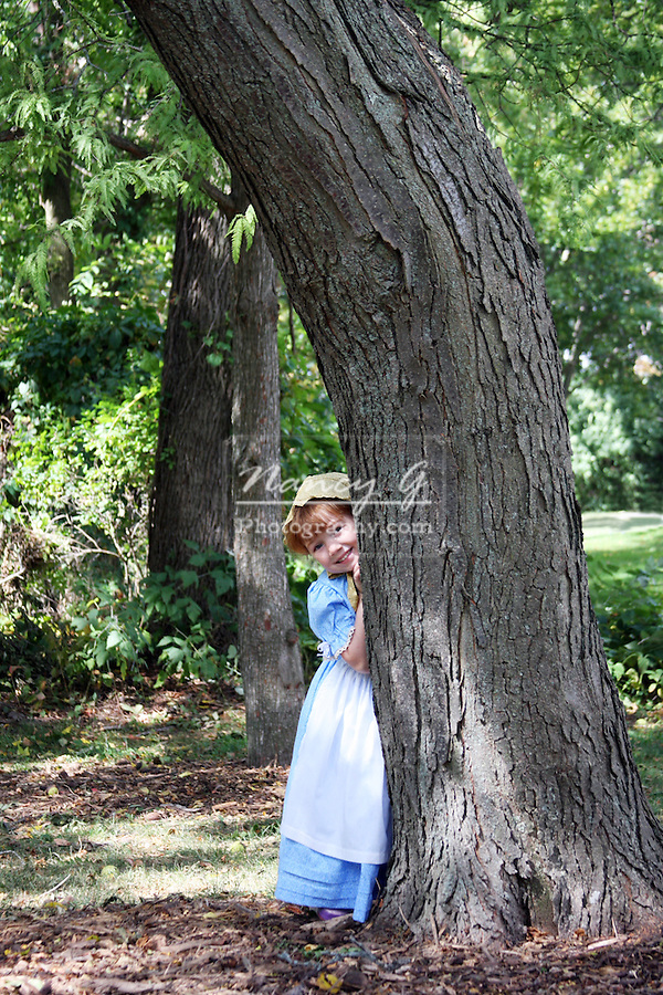 A young girl behind a tree