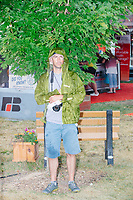 Photographer Daniel Acker stands under a tree in the rain as Republican presidential candidate and former Massachusetts governor Bill Weld speaks at the Political Soapbox at the Iowa State Fair in Des Moines, Iowa, on Sun., August 11, 2019.