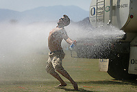 Indio, Ca.- Beating the heat Thursday before the Coachella Valley Music and Arts Festival,  Tony Lynch,24, of Albany, New York cools off behind a water truck after setting up his campsite, Thursday April 26, 2007. Several Thousand music fans are gathering for the festival, held on the Empire Polo Field grounds in Indio. The Coachella Valley Music and Arts Festival, the largest music festival in California, has expanded from two to three days this year.