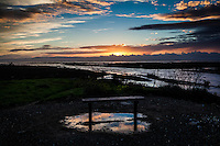 A bench along the shore of San Francisco Bay and under it, a pool reflecting the sky and growing sunset filling the sky overhead.