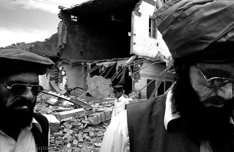 dezaghundai, waziristan, april 2004: staff of a gomal high school return to access damage caused to the school house from missle fired by a pakistan army apache helicopter.  a large number of civilian homes and buildings were fired upon during the pakistan army's short campiagn against suspected al-qaeda fighters and collaborators<br />