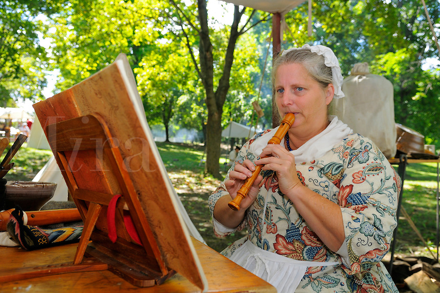 Wife of British redcoat plays an English soprano flute at a Revolutionary War encampment, Fort Ticonderoga, New York, USA.