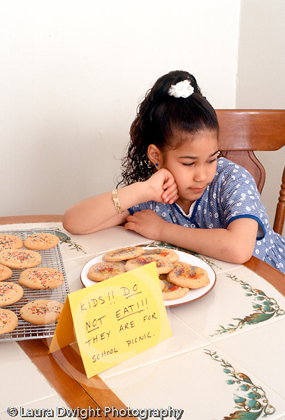 7 year old girl sitting at table unhappy that she can't eat nearby homemake cookies Hispanic Dominican vertical