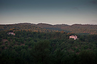 The main house and a guest house which form part of Finca Buenvino seen from across the hillside at dusk