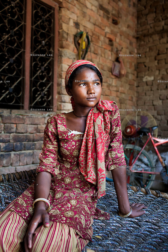 Manju Devi, 15, sits in the compounds of her home in Naraina gaon, Titana village, Samalkha town, Haryana, India on 15th June 2012. Her late father was a snake charmer and her mother has gone through multiple operations to remove a tumor, so she had to drop out of school to look after her siblings and to contribute to the household income by working as a brick carrier from 8am to 5pm in construction sites for INR 25 (USD 0.45)per day. Photo by Suzanne Lee for The National