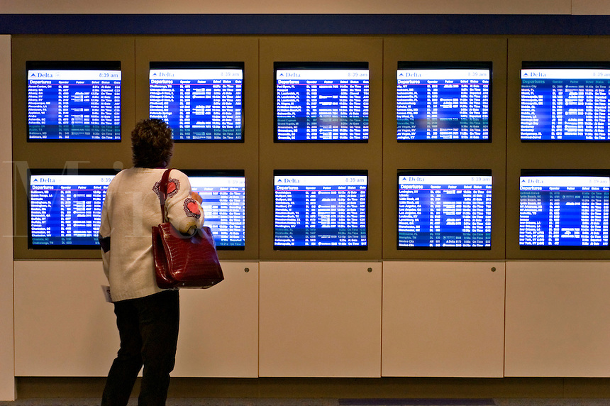 Traveler checks the incoming and departing flights at Atlanta's Hartsfield-Jackson International Airport.