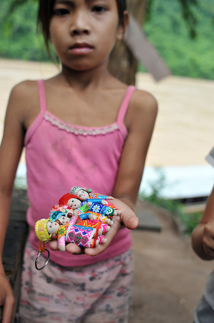 A young girl sells crafts in the streets. -though Laos has been a top-ranked tourist destinations in recent years, the country remains one of the world's poorest nations and relies on foreign aid and donations. Lao people struggle with severe poverty and its life expectancy is extremely low