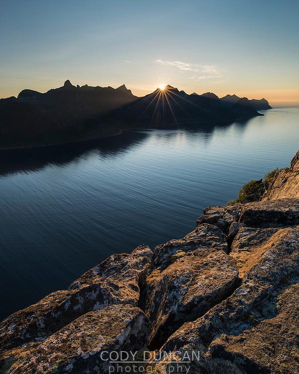 Sun setting across Øyfjord from summit of Riven, Senja, Norway