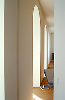 A series of arched windows runs the length of the living room