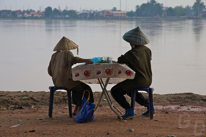 Elderly people overlooking the Mekong River towards Thailand in Vientiane