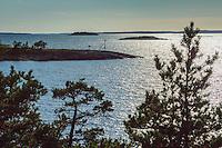 Stångmärke på häll i motljus i Stockholms skärgård. / Seamark in the Stockholm archipelago in Sweden.