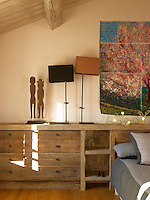 A pair of figurines is placed beside two bedside lamps on the integrated wooden drawers and shelving unit of the master bedroom