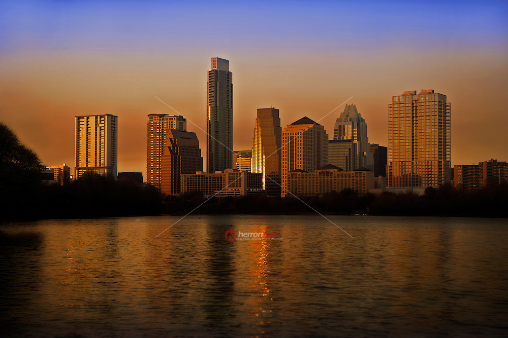 A beautiful afternoon sun shines on the Colorado River next to the Austin Skyline at sunset