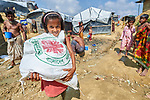 A Rohingya girl carries home a bag of food provided by Caritas in the Mainerghona Refugee Camp near Cox's Bazar, Bangladesh, on October 27, 2017. She is among the more than 600,000 Rohingya who since August have fled government-sanctioned violence in Myanmar for safety in Bangladesh.