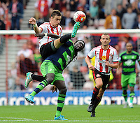 Sebastian Coates of Sunderland gets to the ball ahead of Bafetibis Gomis of Swansea City during the Barclays Premier League match between Sunderland and Swansea City played at Stadium of Light, Sunderland