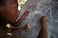 a young guest of a  small orphanage draws on the main black board in the outskirts of Addis Ababa, Ethiopia on Tuesday June 05 2007.