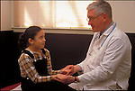 doctor examining hands of young female patient