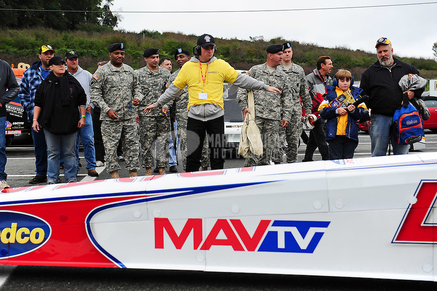 Oct. 2, 2011; Mohnton, PA, USA: An NHRA security guard holds back U.S. Army soldiers as a top fuel dragster is towed through the staging lanes during the Auto Plus Nationals at Maple Grove Raceway. Mandatory Credit: Mark J. Rebilas-