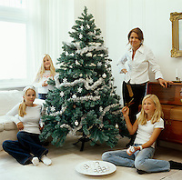 Designer Lena Eriksson with her three daughters Frida, Mina and Moa around a Christmas tree in the drawing room