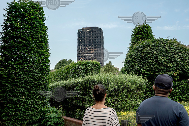 People look at the charred ruins of Grenfell Tower following the fire of 14 June 2017 which rapidly spreaad through the building killing at least 80 people and leaving many more without homes or possessions.
