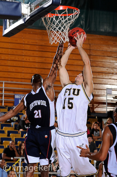 4 November 2009:  FIU's Nikola Gacesa (15) puts up a shot over Northwood's Lester Hunte (21) as Northwood faced off against FIU at the U.S. Century Bank Arena in Miami, Florida.