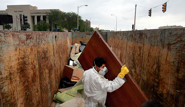 Marcial Leiva of Marsden Building Maintenance places a flood-ruined door in a large dumpster outside the 100 Court Avenue building Sunday morning, June 15, 2008.  Items from the building's basement are being cleaned or thrown out.