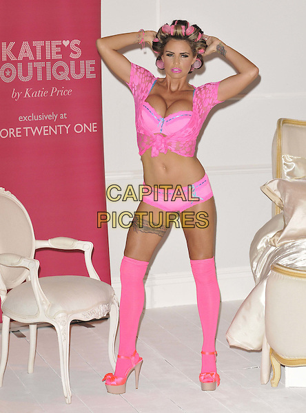 Katie Price (Jordan).The launch photocall for Katie Price's new summer lingerie range for Store 21, The Worx, London, England..May 29th, 2012.full length pink lace top knotted bra cleavage belly stomach midriff knickers underwear tattoo tights stockings garter beige platform sandals shoes rollers curlers in hair hands arms in air.CAP/CAN.©Can Nguyen/Capital Pictures.