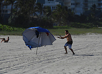 POMPANO BEACH, FL - JULY 31: A Man is seen chasing an umbrella as the wind picks up on Pompano Beach as Hurricane Isaias tracks towards Florida in addition to Florida reporting more than 9,007 new COVID-19 cases Friday and 257 deaths on July 31, 2020 in Pompano Beach, Florida. Credit: mpi04/MediaPunch