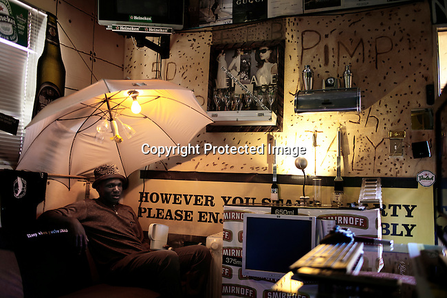 "SOWETO, SOUTH AFRICA DECEMBER 17: Sifiso ""50 cents"" Sithole sits in his room on December 17, 2012 Rockville section of Soweto, South Africa. He runs a car wash and calls himself a pimp and loves everything Italian and fancy brands. He decorated his room with things he collected. Soweto today is a mix of old housing and newly constructed townhouses. A new hungry black middle-class is growing steadily. Many residents work in Johannesburg but the last years many shopping malls have been built, and people are starting to spend their money in Soweto. (Photo by: Per-Anders Pettersson)"