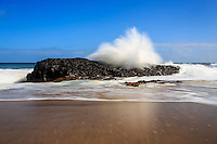 A large wave jumps in a soft spray of a fountain over black volcanic rock on the shore of Lumahai'i Beach, northern Kaua'i.