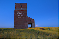 Grain elevator and setting moon in ghost town<br /> Bents<br /> Saskatchewan<br /> Canada