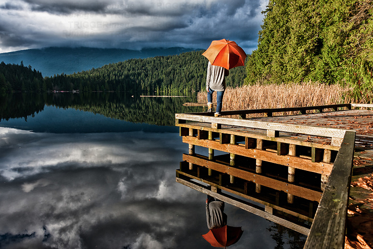 A young woman stands on a wooden jetty holding an orange umbrella while over looking a peaceful lake with forests