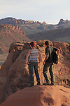 Man and woman visitors at Arches National Park, Moab, Utah, USA. .  John offers private photo tours in Arches National Park and throughout Utah and Colorado. Year-round.
